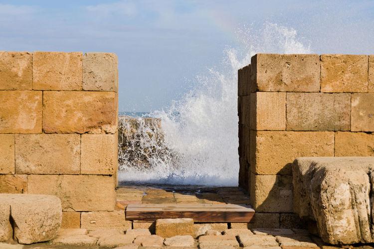 Sea waves splashing on rocks against wall