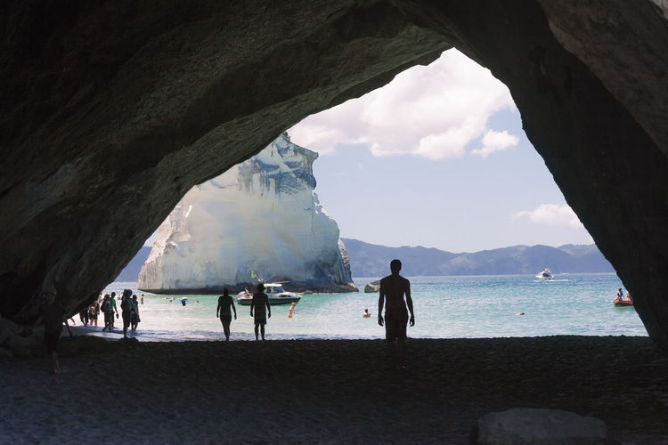 People at beach by rock formation against sky