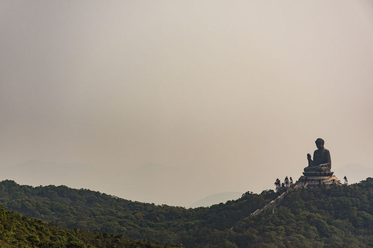 Large buddha statue on mountain against sky
