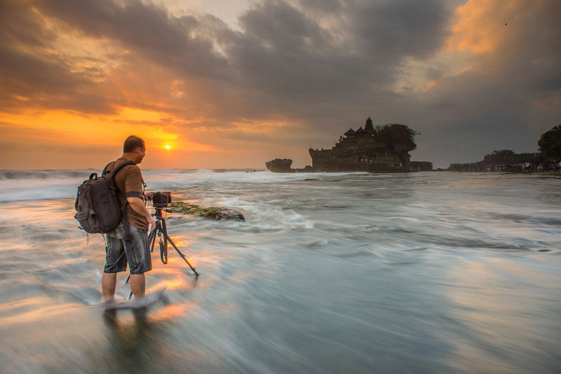 A photographer photographing Sunset at Tanah Lot, a popular tourist attraction in Bali, Indonesia. Architecture Bali Beach Beauty In Nature Clouds Clouds And Sky Cloudscape INDONESIA Island Mature Adult Moss Nature One Person Outdoors Photographer Pura Rock Formation Sea Sunset Sunsets Tanah Lot Temple Tourist Attraction  Tripod Waves