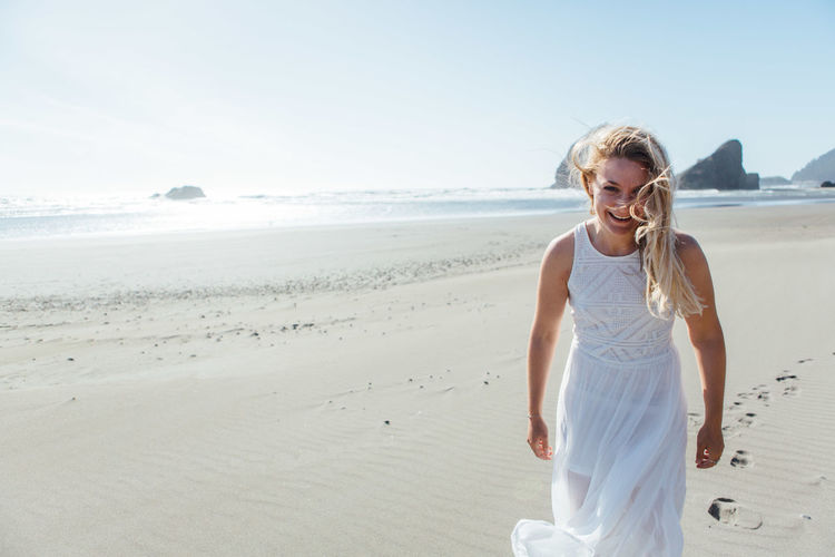 Portrait of smiling young woman standing on beach against clear sky