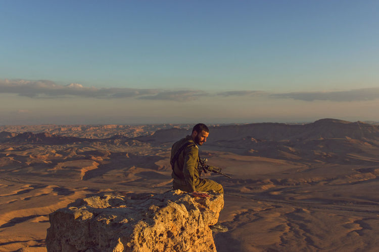 A young soldier is sitting on a rock in front of the crater Mitzpe Ramon. Desert Nature Army Beauty In Nature Crater Environment Landscape One Person Real People Rock - Object Side View Sundown Tranquility Weapon