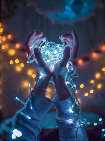Close-Up Of Woman Holding Illuminated Christmas Lights