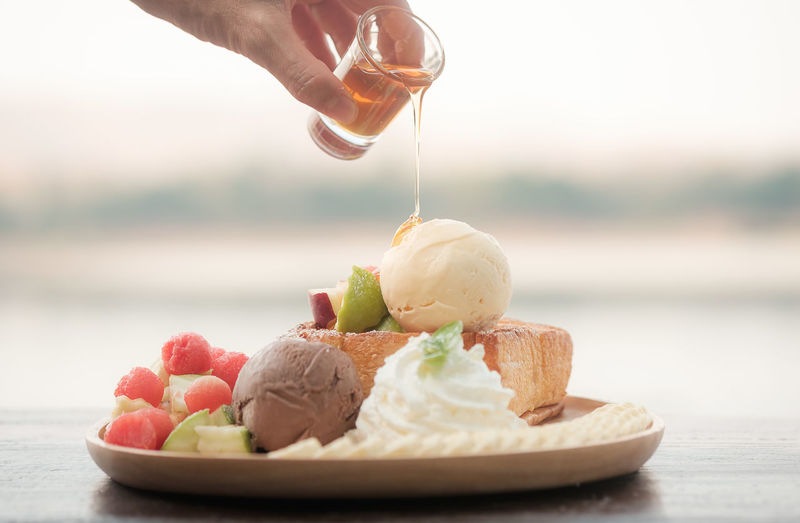 Close-up of hand holding ice cream cone on table