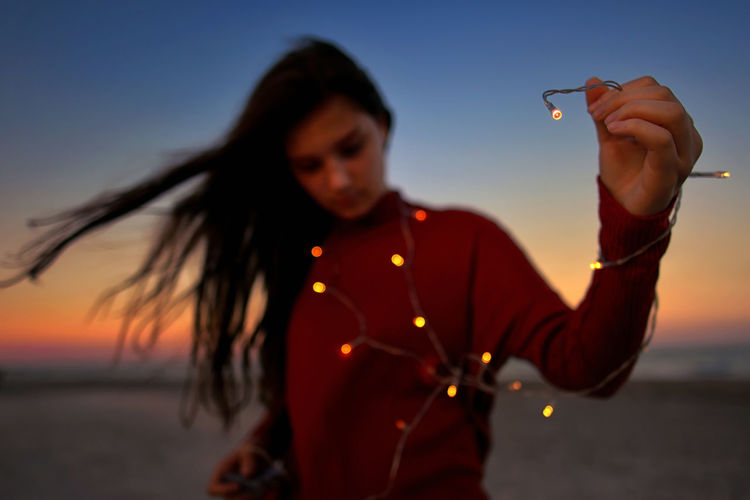 Woman holding illuminated string light while standing at beach during sunset
