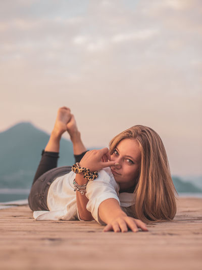 Portrait of woman relaxing at beach against sky