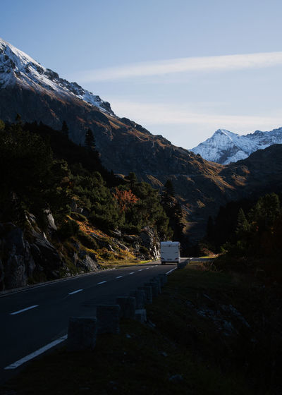 Scenic view of caravan on mountain road against sky