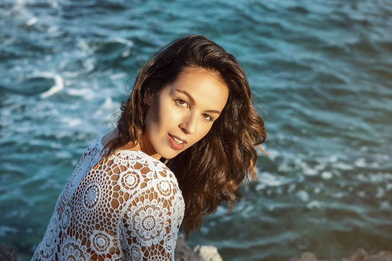 Portrait of smiling woman against sea
