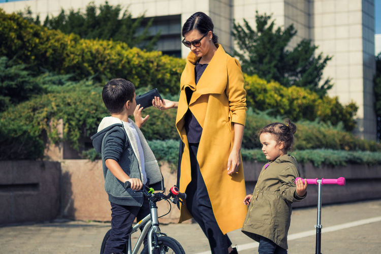 Girl and boy with bicycle standing by mother on road