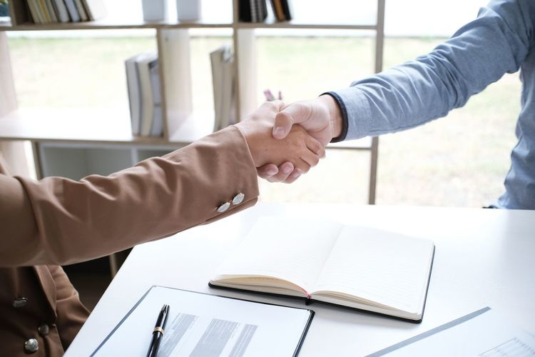 Cropped Image Of Judge Businesswoman Shaking Hands Over Desk