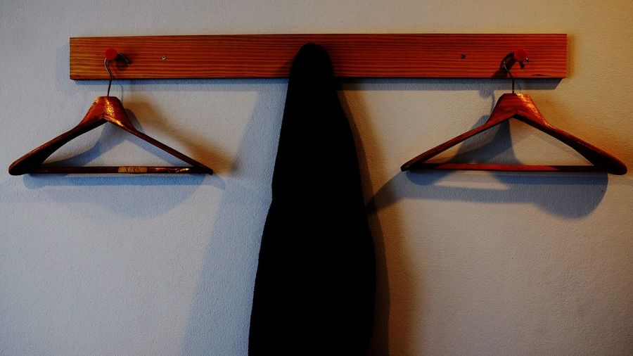 Close-up of coat with hangers hanging on hooks