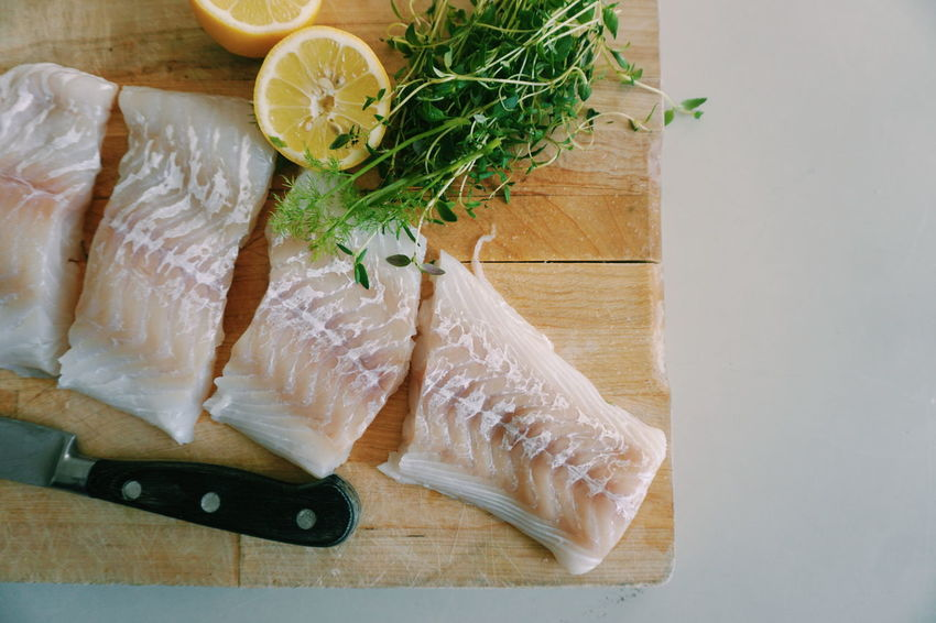 fresh cod fillet on a woodboard together with fresh thyme and lemon Lemon Thyme Cod Fish Fish Raw Preparing Food Top View Top Perspective Herb Cutting Board Preparation  Studio Shot High Angle View Quality Rosemary Kitchen Knife Close-up Food And Drink Dill
