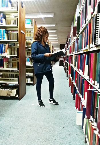 Full length of young woman reading book