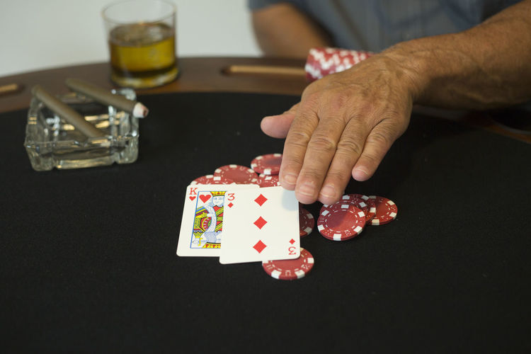 Casino chips and playing cards on a poker table. Arts Culture And Entertainment Cards Food And Drink Gambling Gambling Chip Game Of Chance Glass Hand Holding Human Body Part Human Hand Indoors  Leisure Activity Leisure Games Luck Midsection One Person Opportunity Playing Poker - Card Game Real People Relaxation Table