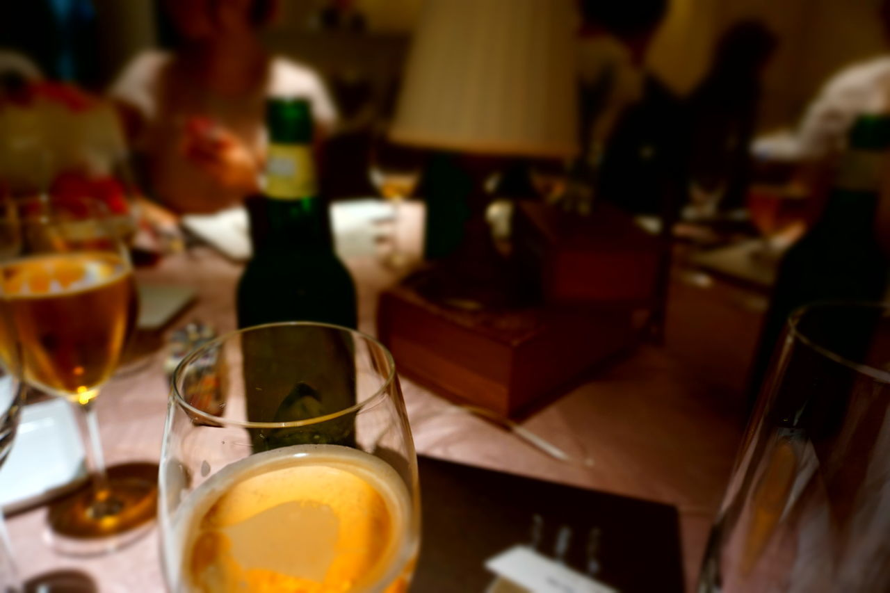 table, indoors, food and drink, drink, restaurant, focus on foreground, no people, close-up, drinking glass, alcohol, freshness, wineglass, illuminated, food, ready-to-eat, day