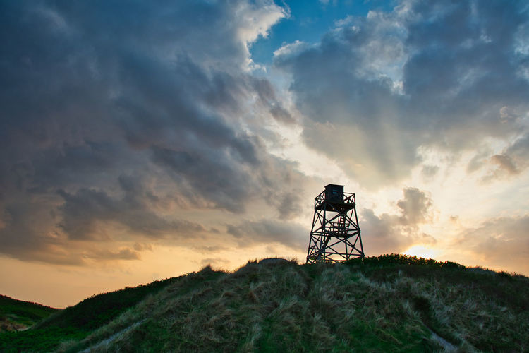 Low angle view of silhouette tower on field against sky