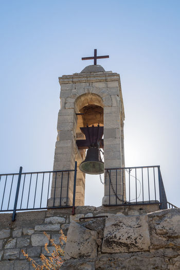 Bar'am, Israel, June 09, 2018 : The belfry with the bell of the functioning church of the Christian Maronites in the abandoned village Kafr Birim in the north of Israel Christian Maronites Church Cross God Jesus Christ Kafr Birim Abandoned Village Arabic Architecture Art Belfry Tower Bible Building Culture Day Heritage History Holy Israel Landmark Monument Old Pry Religion Symbol