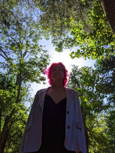 Low angle view of woman standing against trees
