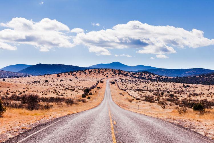 Road amidst desert land against sky