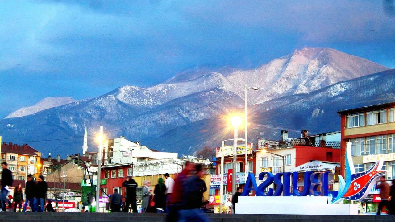 mountain, sky, snow, architecture, built structure, building exterior, winter, outdoors, cloud - sky, cold temperature, large group of people, nature, city life, real people, snowcapped mountain, men, women, city, illuminated, group of people, mountain range, night, people