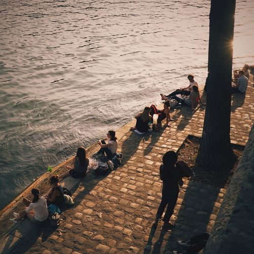 High angle view of people sitting on footpath by sea