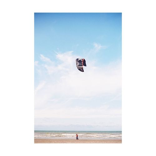 Person paragliding on beach against sky