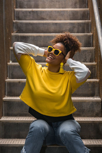 Woman wearing sunglasses while sitting on staircase
