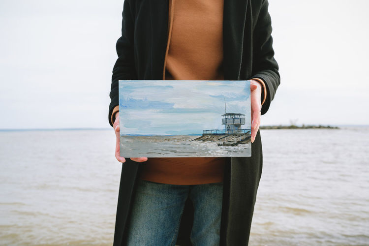 Midsection of woman holding painting against sea and sky