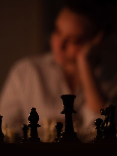 Close-up of man playing on chess board