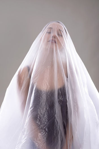 Close-Up Of Woman Covered In Plastic Over Gray Background