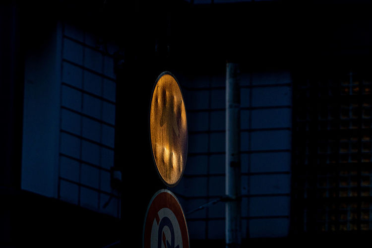 Close-up of illuminated lighting equipment against building
