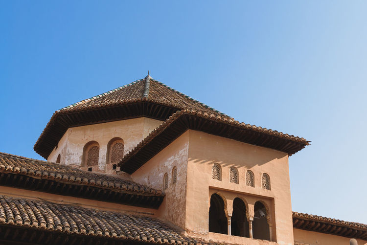 Upper section of an ancient moorish building in the ancient Alhambra in Granada, Spain. Alhambra De Granada  Ancient Andalucía Architecture Moorish Architecture Roof SPAIN Travel Alhambra Architecture Building Building Exterior Buildings Built Structure Day History Low Angle View Moorish Old Old Buildings Outdoors Sky Summer Travel Destinations