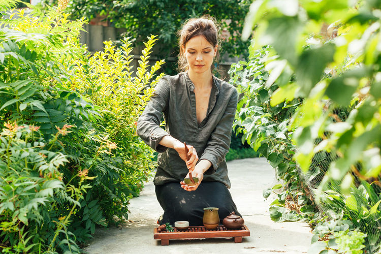 Young woman preparing green tea while sitting on footpath amidst plants