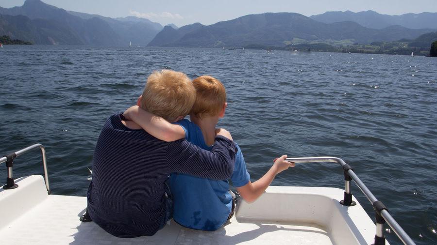 Rear view of siblings sitting in boat on sea