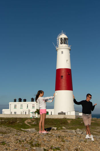 Full length of man and a woman standing by lighthouse against clear blue sky