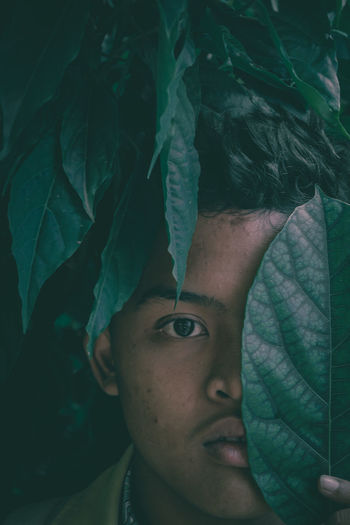 Close-up portrait teenage boy covering eye with leaf