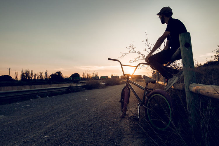 Man riding bicycle on road against sky at sunset