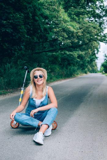 Portrait of teenage girl sitting on road against trees