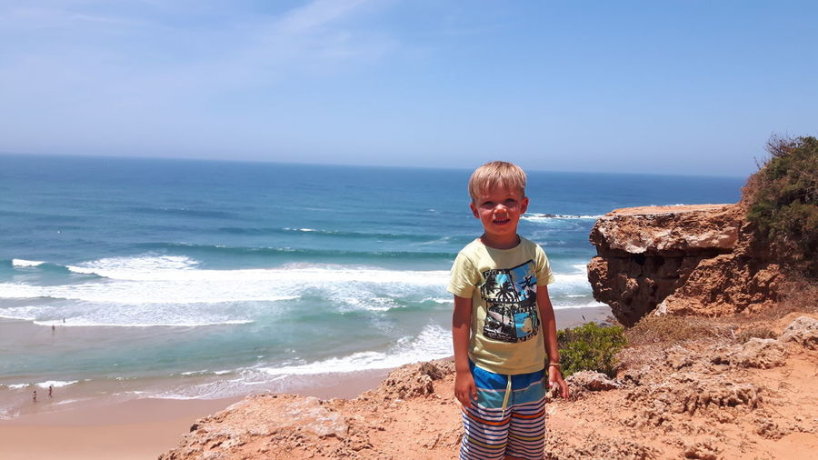 Portrait of boy standing at beach against sky