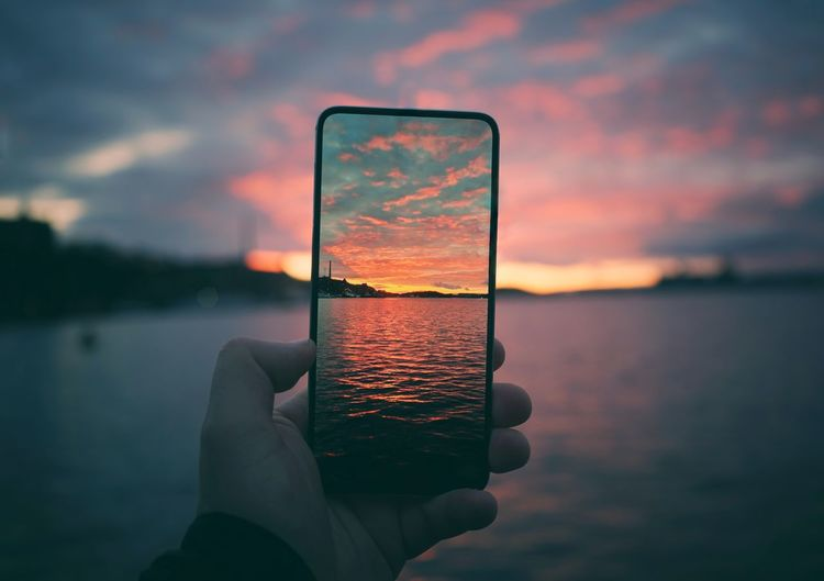 Midsection of person holding smart phone against sky during sunset