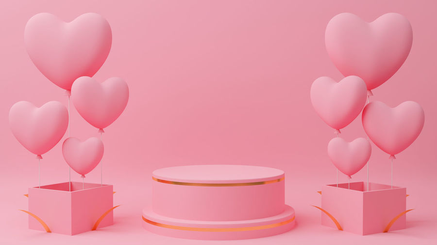 Close-up of pink balloons on table against white background