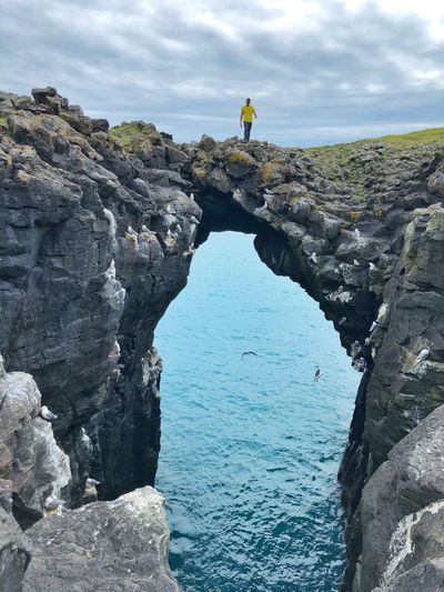 Man standing on natural arch over sea against sky