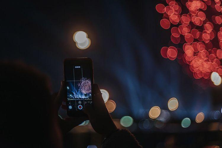 Low angle view of illuminated smart phone at night