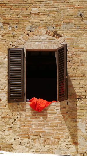 red cloth out of wooden window with shutters on mediterranean wall Red Color Red Cloth Wooden Wooden Window Shutters Brown Window Mediterranean  Mediterranen Wall Still Life Photography EyeEm Gallery Real Life Street Photography Red Wood - Material Window Old-fashioned Architecture Built Structure Summer In The City