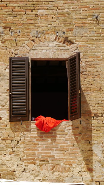 red cloth out of wooden window with shutters on mediterranean wall Red Color Red Cloth Wooden Wooden Window Shutters Brown Window Mediterranean  Mediterranen Wall Still Life Photography EyeEm Gallery Real Life Street Photography Red Wood - Material Window Old-fashioned Architecture Built Structure