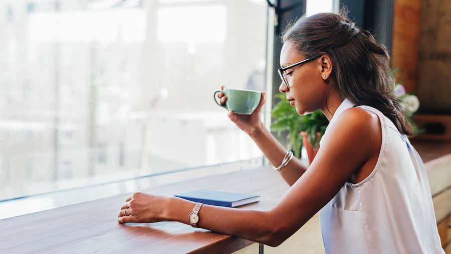 One Person Real People Indoors  Business Person Woman Glasses Working Indoors  Cafe Freelance Life Cup Coffee Copy Space Sitting African American Looking Window Entrepreneur