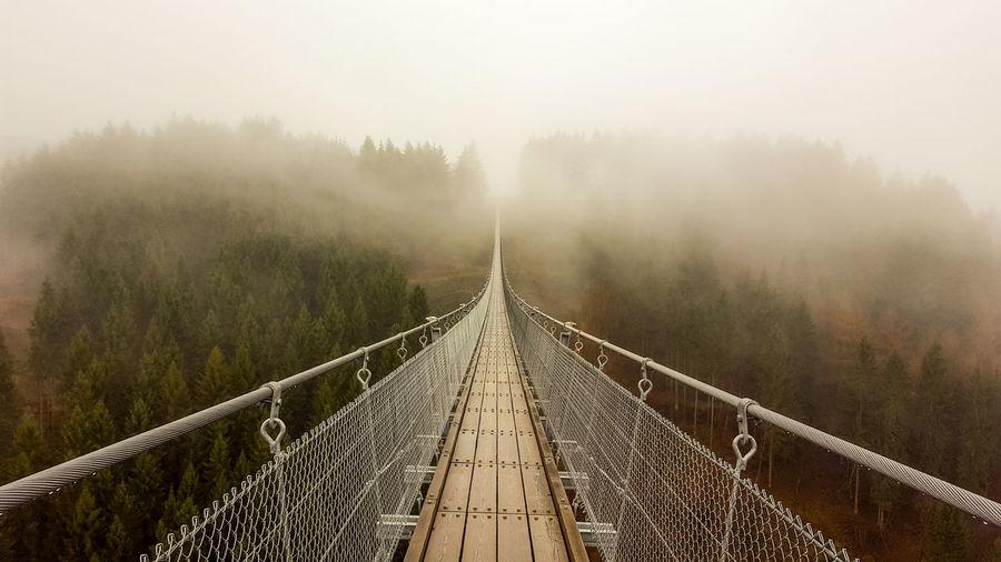 Footbridge amidst trees against sky during foggy weather