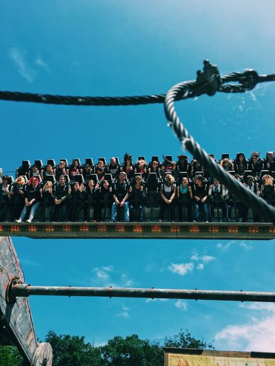 People riding on amusement park ride against sky