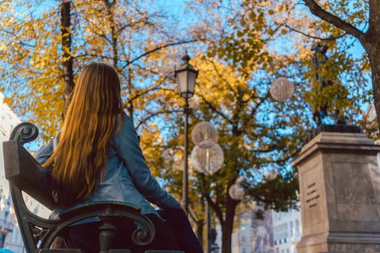 Low angle view of woman sitting on bench against trees