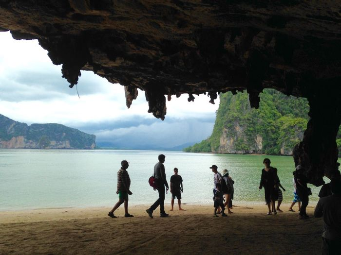 Group of people by cave at beach
